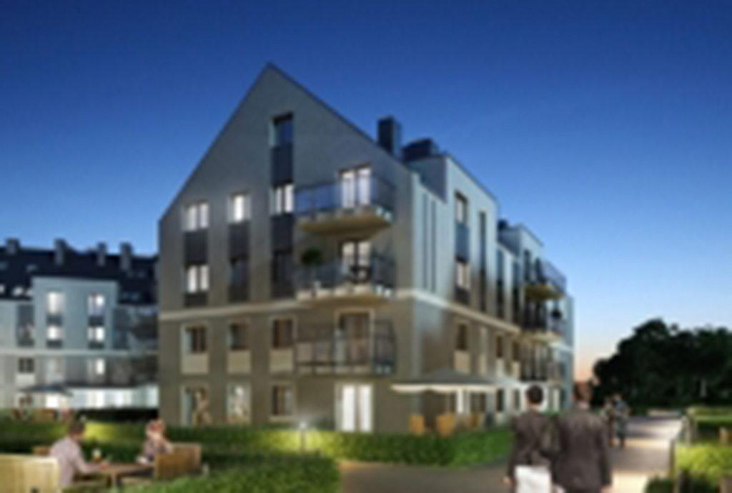 zdjęcie nocą obrazujące luksusowy apartamentowiec we Wrocławiu, gdzie mieści się oferowane mieszkanie do sprzedaży