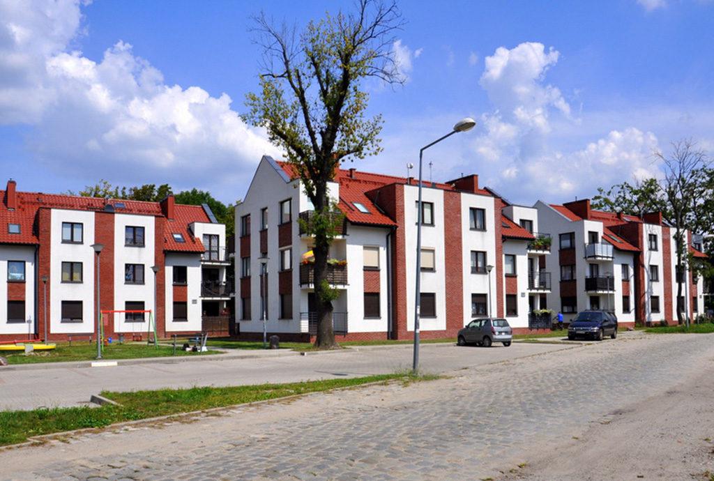 widok od strony ulicy na osiedle we Wrocławiu (okolice), gdzie znajduje się oferowane mieszkanie na sprzedaż
