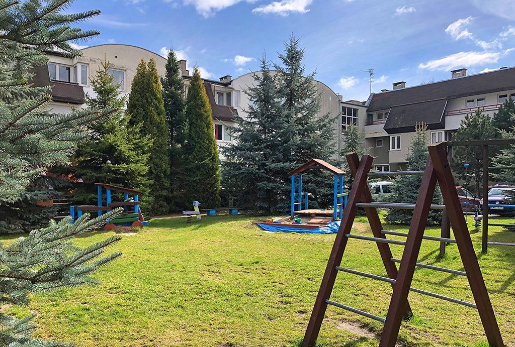 zdjęcie prezentuje plac zabaw przed budynkiem, w którym mieści się oferowane do wynajęcia mieszkanie Wrocław Krzyki